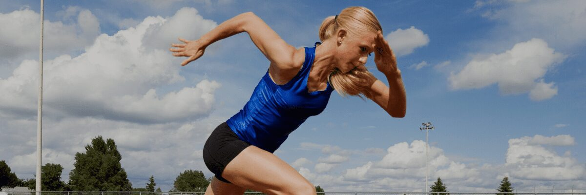 woman running, wearing blue shirt and black shorts, the sky is blue and it's the summer