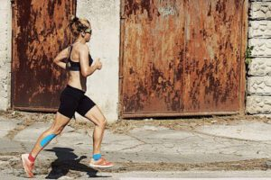 athletic woman running in street with taped shin and ankle
